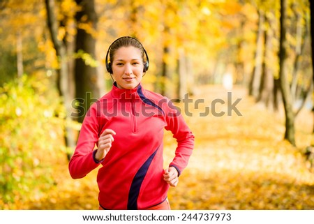 Young woman with headphones  running in autumn nature and listening music - stock photo