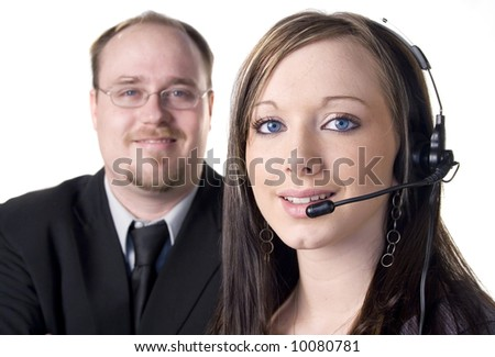 Young woman with headset and man in background on white - stock photo