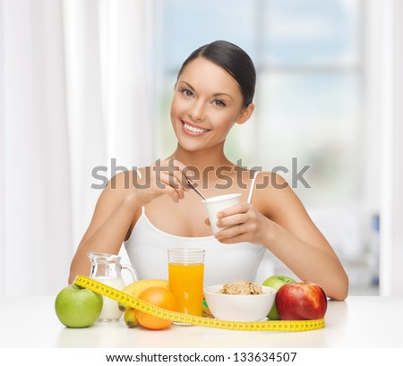 young woman with healthy breakfast and measuring tape - stock photo