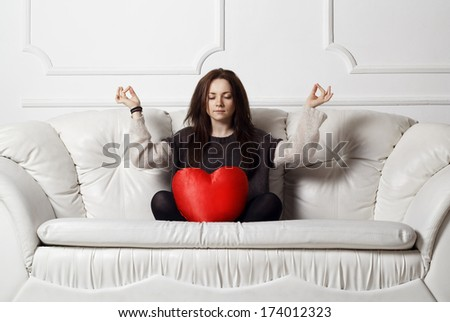 Young woman with heart doing meditation - stock photo