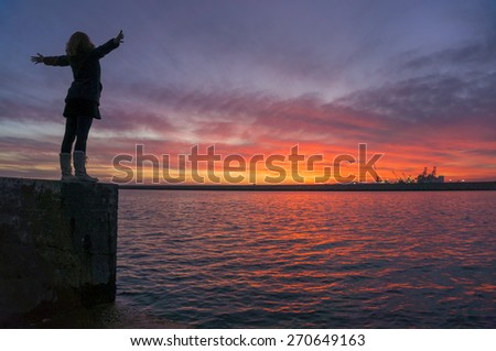 Young woman with her arms up in the air with joy and contentment watching the dreamy sunset over the sea. - stock photo