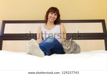 young woman with her cat on the bed at home - stock photo