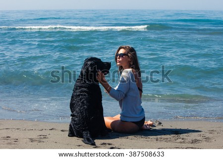 young woman with her dog at sandy sea beach enjoy in summer day - stock photo