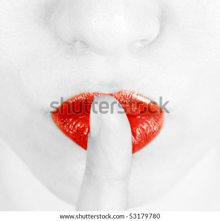 Young woman with her finger on lips - stock photo