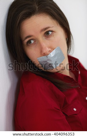 Young woman with her lips being taped over with silver tape - stock photo