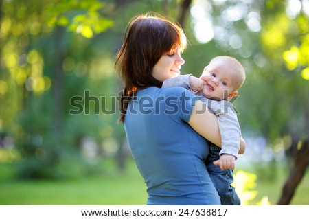 Young woman with her little baby boy at the summer park - stock photo