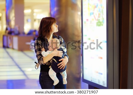 Young woman with her little baby in a shopping mall  - stock photo