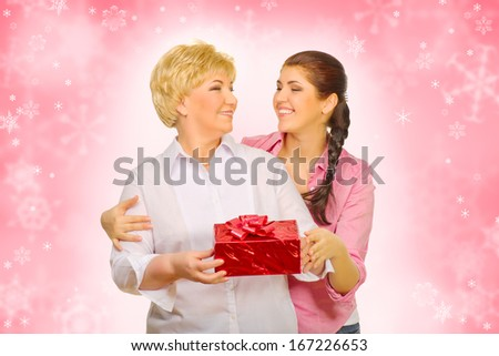Young woman with her mother on red winter background - stock photo