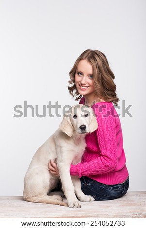 Young woman with her pet, golden retriever in studio - stock photo