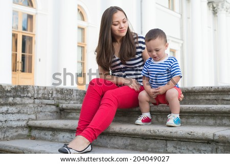 Young woman with her son on the stairs playing - stock photo