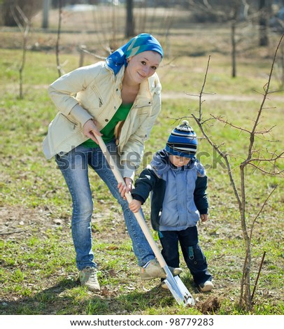 young woman with her son resetting  tree in park - stock photo