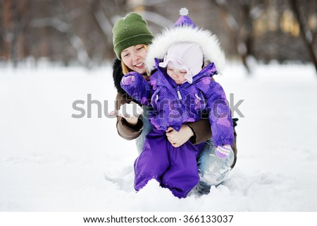 Young woman with her toddler girl at the winter park  - stock photo