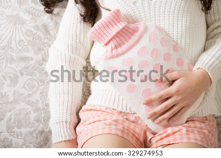 Young woman with hot-water bottle on belly - stock photo
