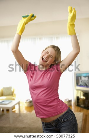 Young woman with housecleaning gear dances in the living room.  Vertical shot. - stock photo