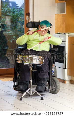 Young woman with infantile cerebral palsy caused by complications at birth sitting in a multifunctional wheelchair playing a drum for spastic therapy with a happy smile - stock photo