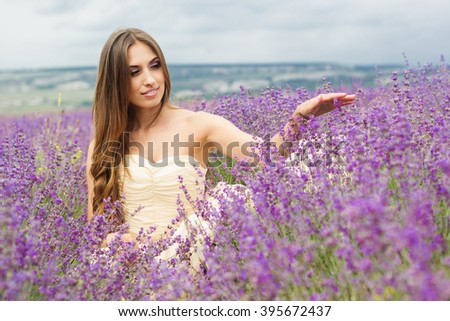 Young woman with is wearing nice white dress at field of purple lavender flowers  - stock photo