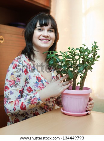 Young woman with  jade in flowering pot at her home - stock photo