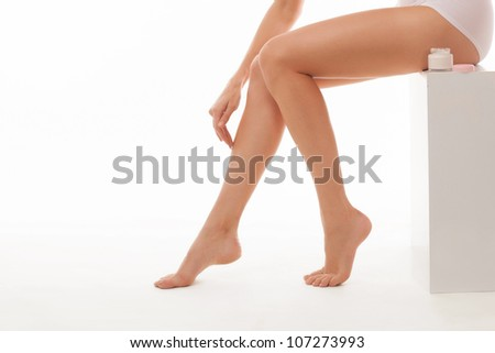 Young woman with jar of body lotion - stock photo