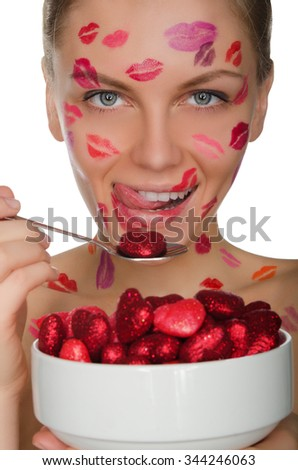 young woman with kisses on face eats hearts isolated on white - stock photo
