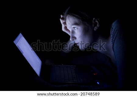 Young woman with laptop at night - stock photo