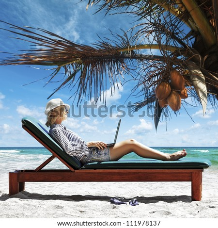 Young woman with laptop at the beach - stock photo