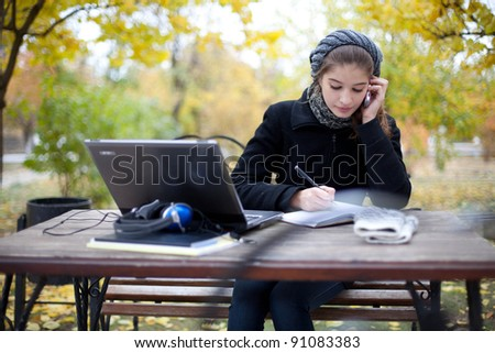 young woman with laptop computer in park - stock photo