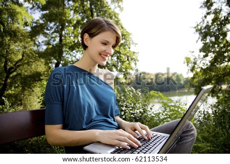 young woman with laptop in park relaxing in the sunshine - stock photo