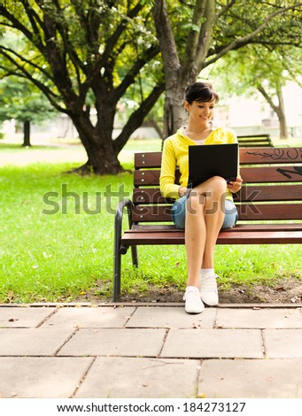 young woman with laptop in the park, full lenght - stock photo