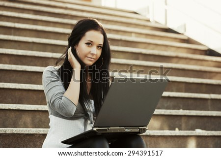 Young woman with laptop on the steps - stock photo