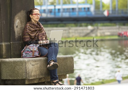Young woman with laptop outdoors. - stock photo