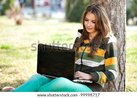young woman with laptop, relaxing in the park - stock photo