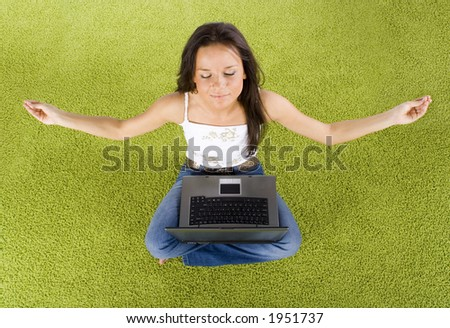 young woman with laptop relaxing on the green carpet - stock photo