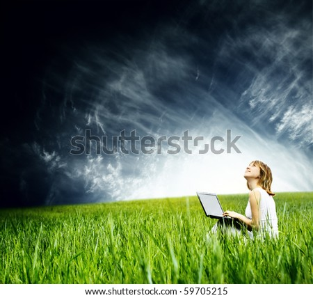 Young woman with laptop sitting on green grass and looking to the sky - stock photo