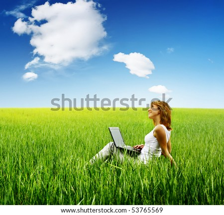 Young woman with laptop sitting on green grass under cloudy sky - stock photo