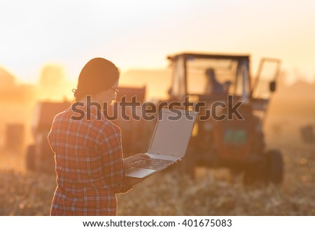 Young woman with laptop standing on field in sunset while tractor baling in background - stock photo