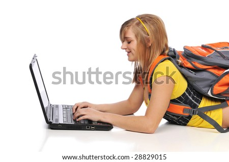 Young woman with laptop typing lying on the floor - stock photo