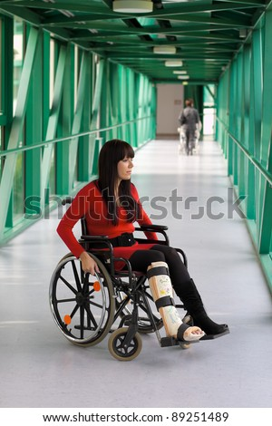young woman with leg in plaster and wheelchair in the hospital - stock photo