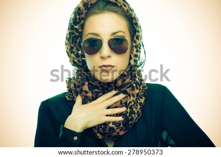 Young woman with leopard pattern scarf and sunglasses - stock photo