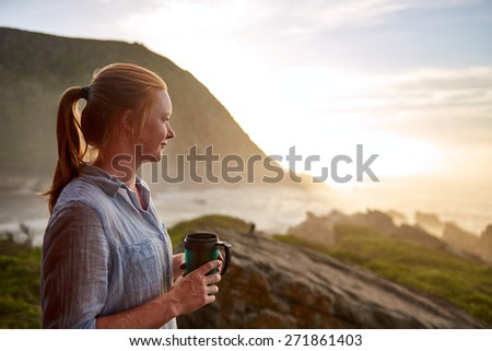 Young woman with light ginger hair and a fresh beauty, standing quietly with a flask of coffee in the early morning, looking out at a picturesque coastline - stock photo