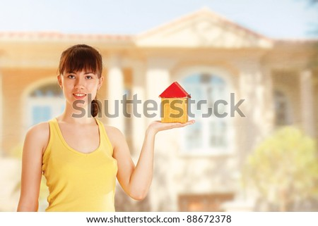 young woman with little house - stock photo