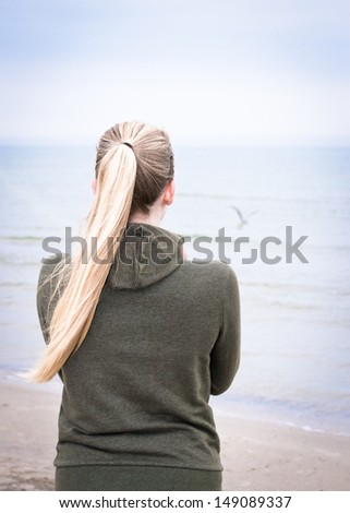 Young woman with long blond ponytail on a foggy morning looking at the sea. There is a gull above the water, but you can see only light shade of it.  - stock photo