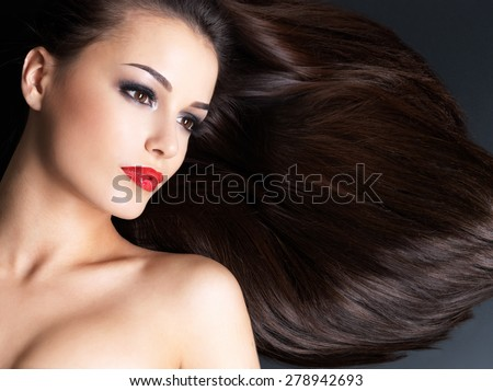 Young woman with long brown straight hairs on a dark background - stock photo