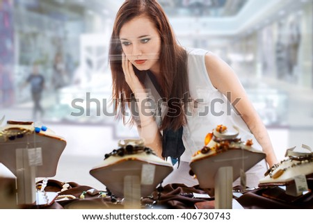 young woman with long dark hair chooses bijouterie in the shop window - stock photo
