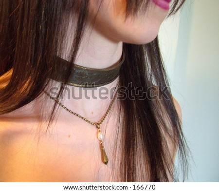 Young woman with long dark hair wearing metal choker - stock photo