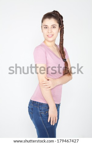 Young woman with long plait wearing in casual clothes: pink t-shirt and blue jeans - stock photo
