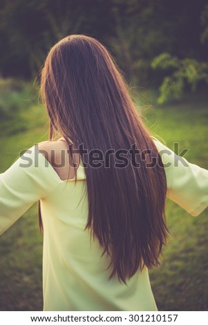 young woman with long straight hair, back shot, outdoor in park, retro colors - stock photo