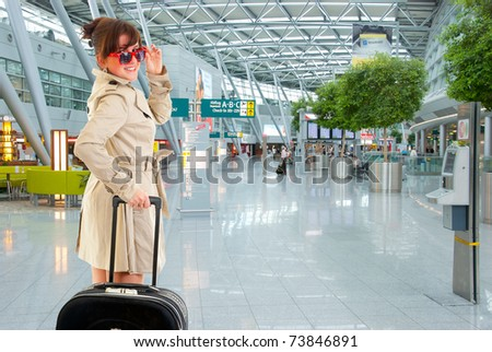 Young woman with luggage at the international airport - stock photo