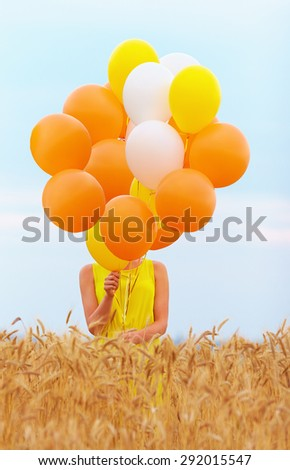 young woman with many balloons on summer wheat field - stock photo