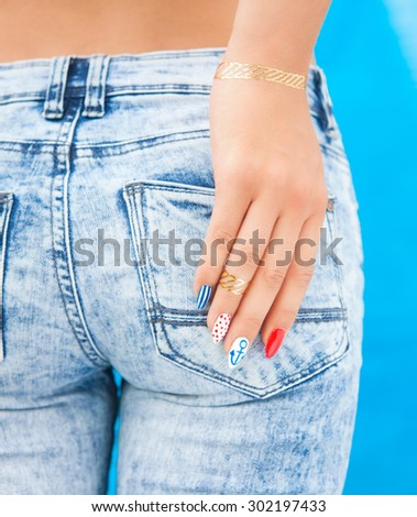 Young woman with marine sailor gel nails manicure holding hand at jeans back pocket - stock photo
