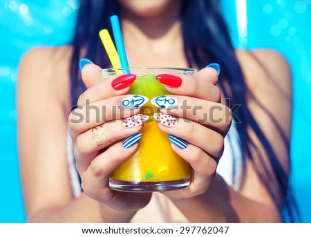 Young woman with marine sailor manicure holding glass of orange juice, summer nail art beauty and drink concept - stock photo